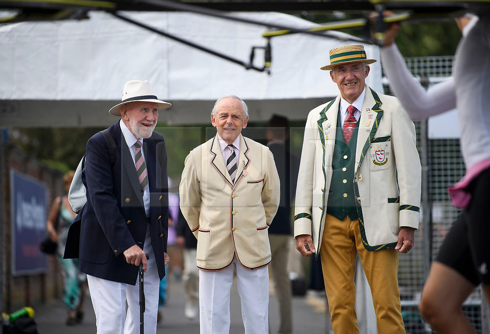 © Licensed to London News Pictures. 04/07/2018. Henley-on-Thames, UK. Three elderly men wearing rowing club jackets watch day one of the Henley Royal Regatta, set on the River Thames by the town of Henley-on-Thames in England. Established in 1839, the five day international rowing event, raced over a course of 2,112 meters (1 mile 550 yards), is considered an important part of the English social season. Photo credit: Ben Cawthra/LNP