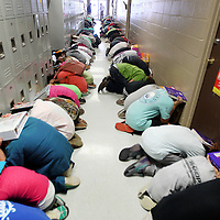 Adam Robison | BUY AT PHOTOS.DJOURNAL.COM<br /> Students at Mooreville Middle School take cover with textbooks over their head dueing a tornado drill Wednesday morning.