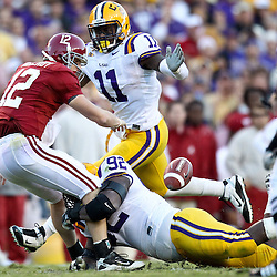 November 6, 2010; Baton Rouge, LA, USA; Alabama Crimson Tide quarterback Greg McElroy (12) fumbles as LSU Tigers defensive tackle Drake Nevis (92) and linebacker Kelvin Sheppard (11) pressure during the second half at Tiger Stadium. LSU defeated Alabama 24-21.  Mandatory Credit: Derick E. Hingle