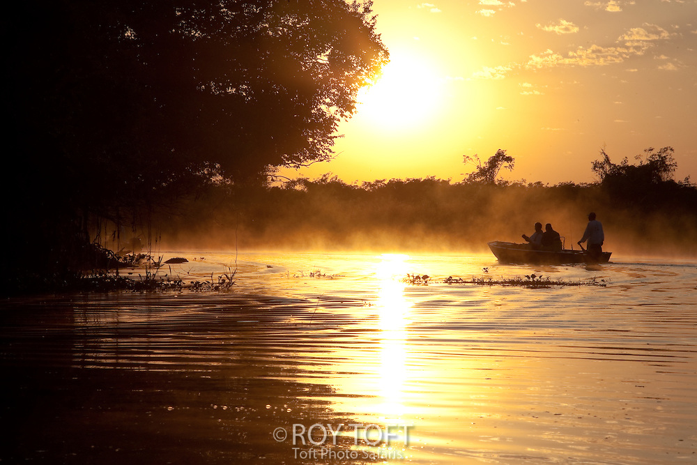 Silhouette of three men in fishing boat at sunrise, Pantanal, Brazil