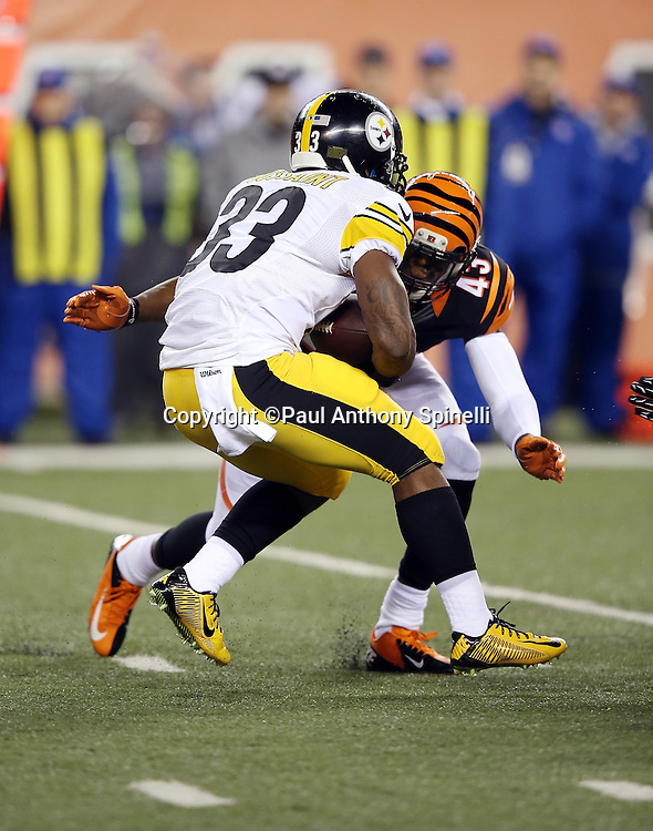 Pittsburgh Steelers running back Fitzgerald Toussaint (33) gets tackled by Cincinnati Bengals strong safety George Iloka (43) during the NFL AFC Wild Card playoff football game against the Cincinnati Bengals on Saturday, Jan. 9, 2016 in Cincinnati. The Steelers won the game 18-16. (©Paul Anthony Spinelli)