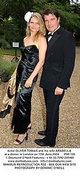 Actor OLIVER TOBIAS and his wife ARABELLA at a fund raising event for The Galapagos Conservation Trust entitled 'Some Enchanted Evening' at the Chelsea Physic Garden Chelsea, London on 17th June 2004.