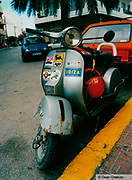 Scooter parked on the street with assorted stickers stuck on the front Ibiza 1998