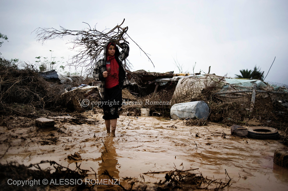 Palestinians walk in a flooded area in the central Gaza Strip following heavy rains on January 19, 2010. Dozens of homes and farms south of Gaza City were inundated by flood waters overnight as heavy rains drenched parts of the Middle East, Palestinian officials and witnesses said. The rising waters flooded some 30 homes in Wadi Gaza, a farming area south of Gaza City mostly inhabited by Bedouins, as Islamist Hamas-run security forces worked through Monday night to evacuate residents, they said.<br /> &copy; ALESSIO ROMENZI