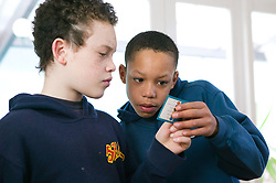 Two boys reading a question card whilst playing a game of Trivia Pursuit,