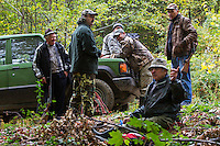 Romanian hunters having a snack at their 4WD cars after a driving hunt for Wild boar (Sus scrofa) in the forest area outside the village of Mehadia, Caras Severin, Romania.