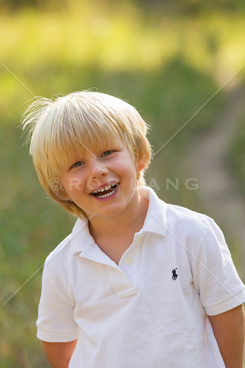 little blond boy smiling outdoors