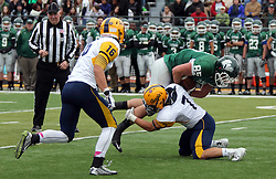 18 October 2014:  John Bastian tails ball carrier Brady Hails with Jack Asquini crouched to make a hit during an NCAA division 3 football game between the Augustana Vikings and the Illinois Wesleyan Titans in Tucci Stadium on Wilder Field, Bloomington IL