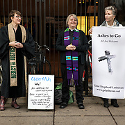 "ALEXANDRIA, VA - MAR1: Pastor Robin Anderson (left) offers ""glitter ashes"" for Ash Wednesday, alongside Pastor Jeanette Leisk (middle) and Linda Schuessler, who were offering traditional ashes, outside the Braddock Road metro station, in Alexandria, VA, March 1, 2017. Across the country, churches involved with the advocacy group Parity will be giving out ""glitter ashes"" to demonstrate that LGBT people should be included in Christianity.(Photo by Evelyn Hockstein/For The Washington Post)"