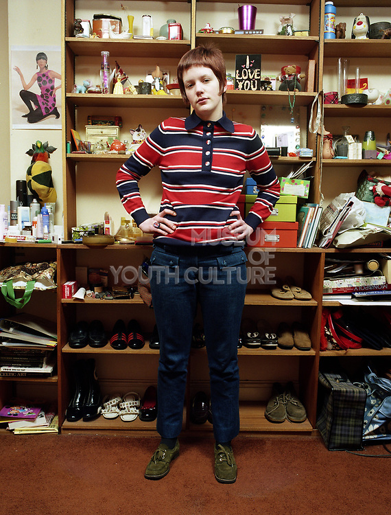 Young Mod woman standing with hands on hips in front of shelves with rows of shoes and knick knacks.