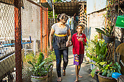28 MARCH 2013 - BANGKOK, THAILAND: Michelle Kao walks through her neighborhood with Pu, a girl who lives in the neighborhood.    PHOTO BY JACK KURTZ
