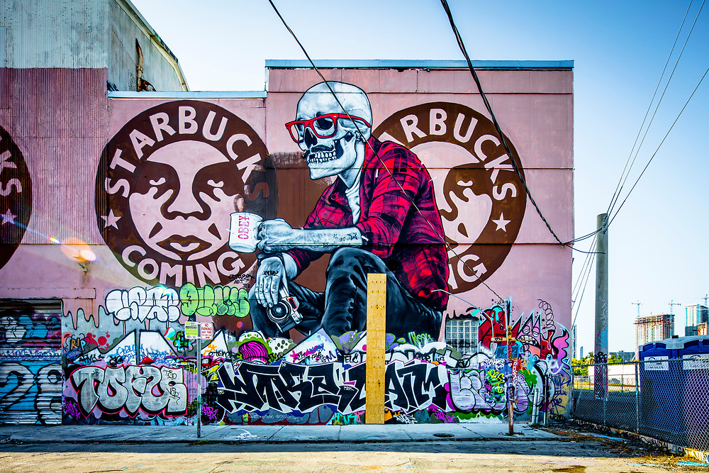 Mural and graffiti on a Miami building with elements by Shepard Fairey and other street artists