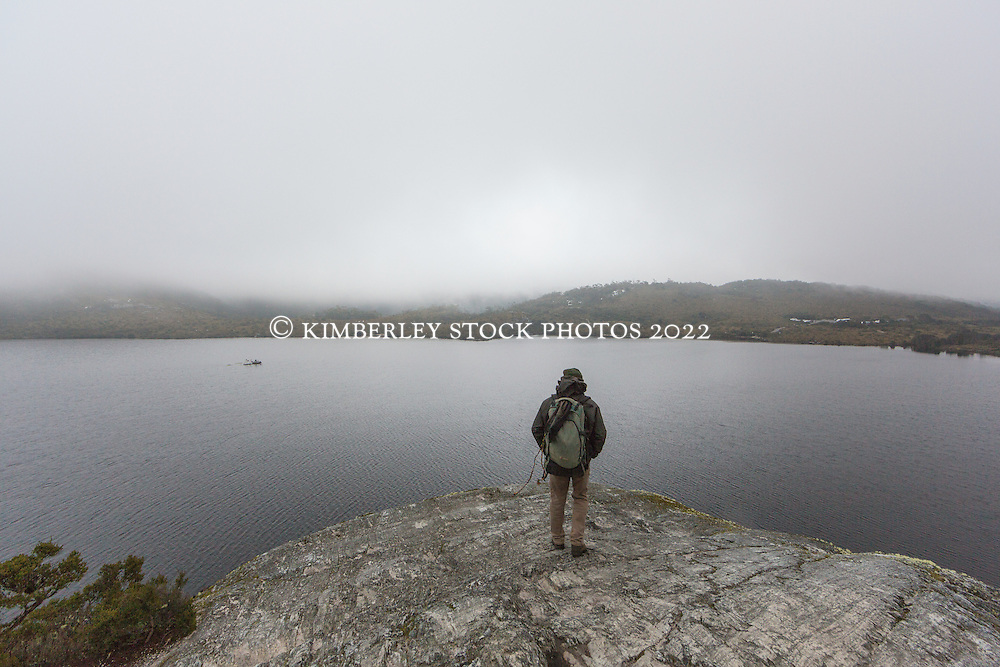 A hiker stands on Glacier Rock, overlooking Dove Lake in the Cradle Mountain-Lake St Clair National Park.