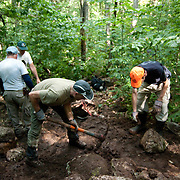 Members of Trailwrights, a club of volunteers who repair and build hiking trails around New England, build a rock step on The Pemmigiwasett Trail in Franconia Notch, NH.