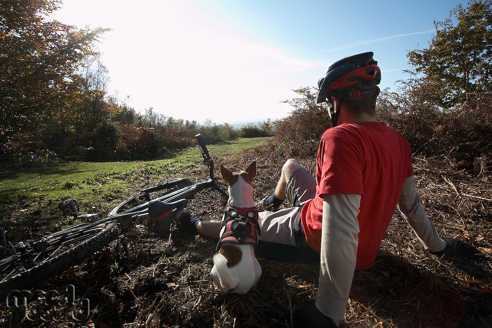 Mountain biker and dog sitting beside bike in countryside