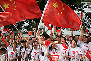 A crowd cheers and waves Chinese flags at the Olympic Torch relay in the southern city of Wuhan