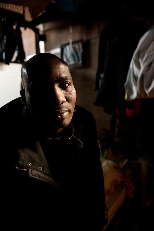 Mery zittend op zijn bed in een gemeenschapelijke slaapzaal. Hij komt uit Mali, is automonteur, en repareert zwart auto's bij een autosloperij. .Sinds 2011 wonen 150 Afrikaanse migranten in een voormalige fabriek in de Parijse voorstand Montreuil, omdat ze illegaal in Frankrijk verblijven, kunnen ze geen woonruimte huren. In het 450 m2 grote pand wonen jonge mannen uit Malië, Ivoorkust, Bukina Faso, Niger.