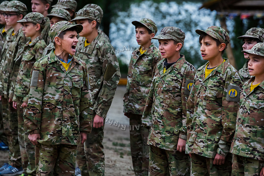 At the call of a team's leader, youngsters participating to the ultra-nationalistic Azovets children's camp are responding with their team's slogan, during a regular ceremony - starting and ending the day - on the banks of the Dnieper river, in Kiev, Ukraine's capital.