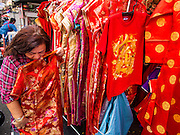 "17 FEBRUARY 2015 - BANGKOK, THAILAND:  Women shop for Chinese New Year outfits at a street stall on Yaowarat Road in Bangkok's Chinatown district. Chinese New Year is February 19 in 2015. It marks the beginning of the Year of Sheep. The Sheep is the eighth sign in Chinese astrology and the number ""8"" is considered to be a very lucky number. It symbolizes wisdom, fortune and prosperity. Ethnic Chinese make up nearly 15% of the Thai population. Chinese New Year (also called Tet or Lunar New Year) is widely celebrated in Thailand, especially in urban areas like Bangkok, Chiang Mai and Hat Yai that have large Chinese populations.      PHOTO BY JACK KURTZ"
