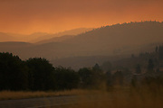 The sun barely illuminates the land under a thick fog of red smoke as seen from Highway 97 just south of Okanogan Friday August 21, 2015.<br />