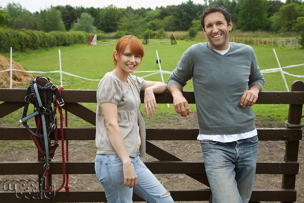 Couple by fence in countryside portrait