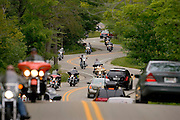 Cars and motorcycles head down a curvy road leading to the ferry dock at Northport to take them to Washington Island.  The ferry boats run between the tip of the Door County Wisconsin peninsula and Washington Island.