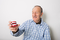 Happy senior man holding dentures against gray background