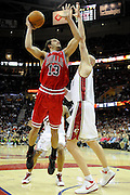 Apr 19, 2010; Cleveland, OH, USA; Chicago Bulls center Joakim Noah (13) shoots over Cleveland Cavaliers center Zydrunas Ilgauskas (11) during the fourth period in game two in the first round of the 2010 NBA playoffs at Quicken Loans Arena. The Cavaliers beat the Bulls 112-102. Mandatory Credit: Jason Miller-US PRESSWIRE