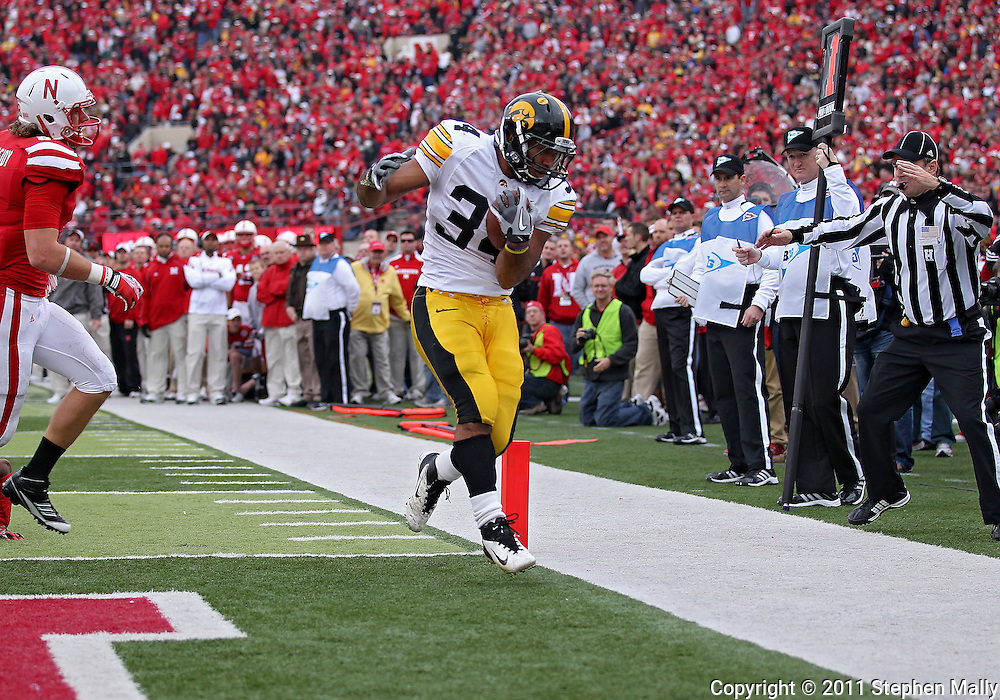 November 25, 2011: Iowa Hawkeyes running back Marcus Coker (34) scores a touchdown on a run as Nebraska Cornhuskers safety Austin Cassidy (8) looks on during the second half of the NCAA football game between the Iowa Hawkeyes and the Nebraska Cornhuskers at Memorial Stadium in Lincoln, Nebraska on Friday, November 25, 2011. Nebraska defeated Iowa 20-7.