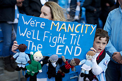 """MANCHESTER, ENGLAND - Monday, April 30, 2012: A Manchester City supporter with a banner """"We're Man City We'll Fight Til' the end (sic)"""" during the Premiership match against Manchester United at the City of Manchester Stadium. (Pic by David Rawcliffe/Propaganda)"""