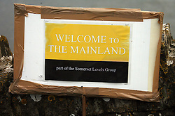 "© London News Pictures. 25/02/2014. Langport, UK. A sign reading ""WELCOME TO THE MAINLAND"" next to the flood covered road to Muchelney from Langport on the Somerset Levels. The area is still suffering from the effects of severe flooding. Photo credit: Jason Bryant/LNP"