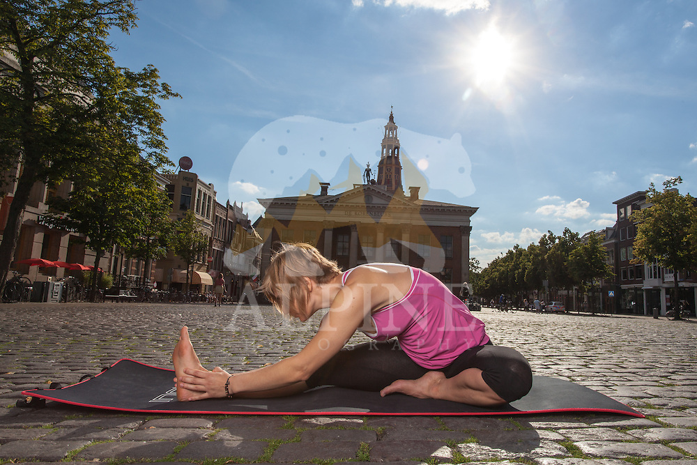 A female athlete as seen practising yoga poses in the very heart of the old town district of Groningen.