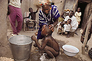 Soumana Natomo and the rest of his family watch as Mamadou, 3, is given his bath. Because Fatoumata Toure, the household's second wife is still nursing a baby, Pama Kondo, the first wife, carries all the water from the village well for the family's use. In the village of Kouakourou, Mali, on the banks of the Niger River. Published in Material World, page 19.
