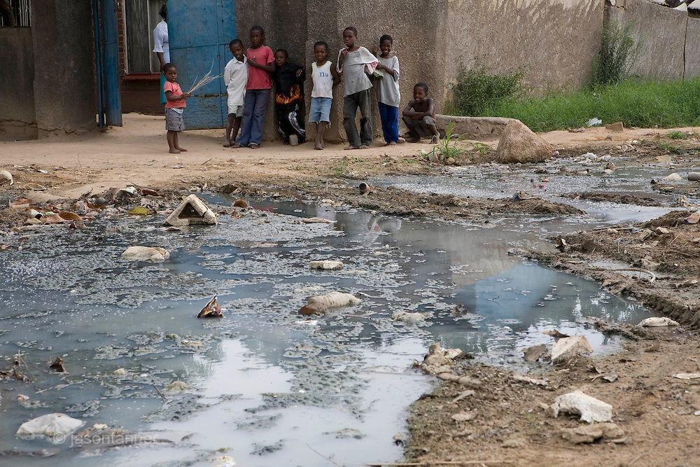 Raw sewage spills onto a street from a burst sewer main in the high density suburb of Chitungwiza on the outskirts of Harare......