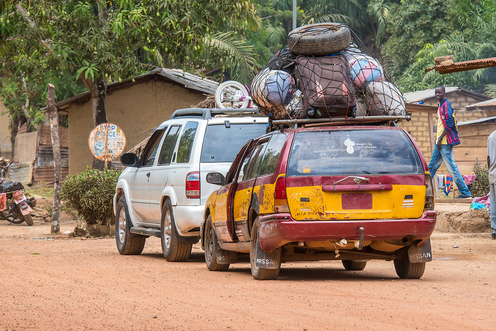 Two vehicles park along dirt road with luggage and other household items packed tightly on roof of worn car, Republic of Guinea