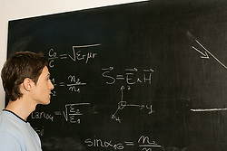Dec. 15, 2012 - Young man contemplating equation on blackboard (Credit Image: © Image Source/ZUMAPRESS.com)