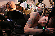 A young woman is being tattooed at one of the artists' stalls at the 2nd International Tattoo Convention in London on Saturday, Oct. 7, 2006, in London, UK. With over 15.000 visitors in three days during the 2005 edition, the event placed London in a central position in the tattoo world.  This year about 150 artists ,representing all the tattoo styles, are ticking away with their machines in a very exciting atmosphere. **ITALY OUT**....