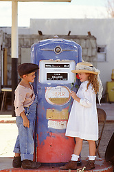 two children dressed in vintage clothing at by an old gas pump