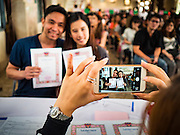 """14 FEBRUARY 2017 - BANGKOK, THAILAND:  A couple has their wedding photo taken with their iPhone in the Bang Rak district in Bangkok. Bang Rak is a popular neighborhood for weddings in Bangkok because it translates as """"Village of Love."""" (Bang translates as village, Rak translates as love.) Hundreds of couples get married in the district on Valentine's Day, which, despite its Catholic origins, is widely celebrated in Thailand.     PHOTO BY JACK KURTZ"""
