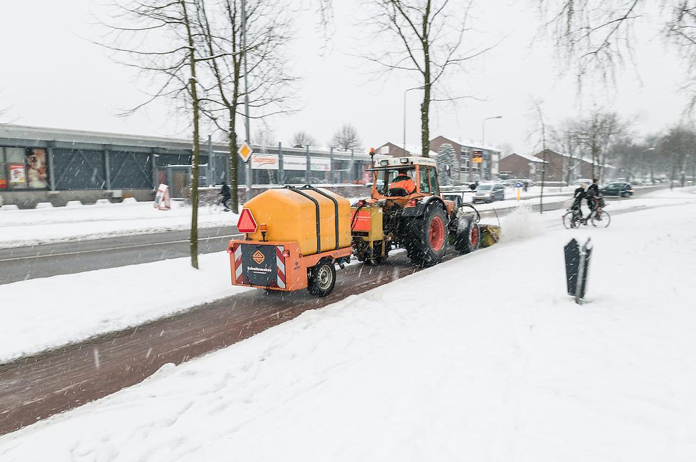 Nederland, Den Bosch, 20130115..In de gemeente Den Bosch worden fietspaden sneeuwvrij gemaakt met een roterende borstel voor op een tractor. Achter de tractor strooit een machine zout om zo de gladheid te bestrijden..Netherlands, Den Bosch, 20130115. In the municipality of Den Bosch cycle lanes are cleaned from snow with a rotating brush in front of a tractor. Behind the tractor salt is sprinkled on to the lanes..