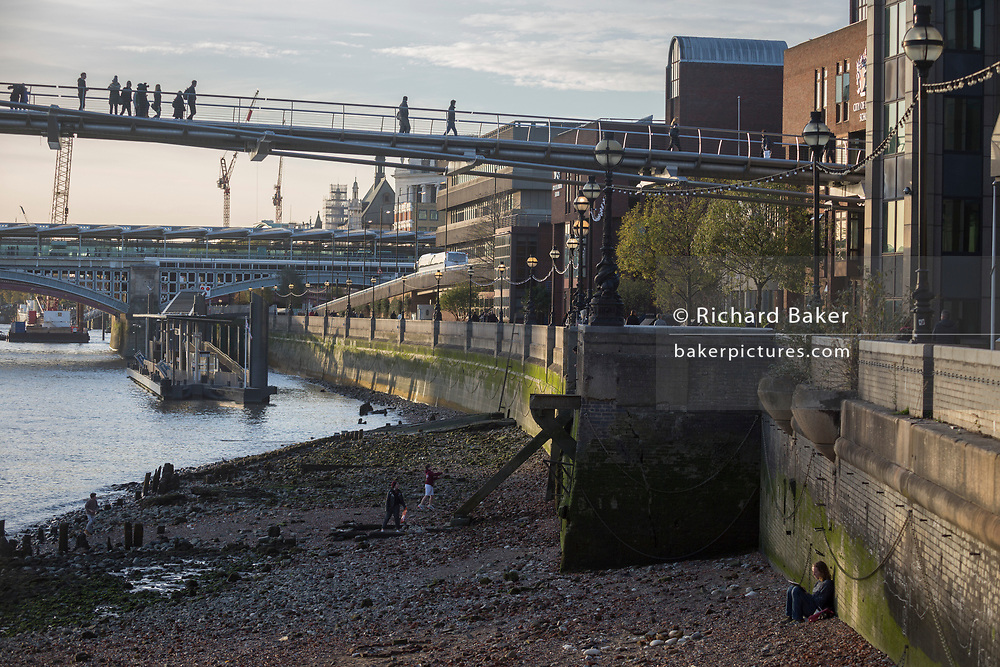 An artist sits against the riverside wall and others play on the low-tide mud as pedestrians on the Millennium Bridge walk overhead, on 30th October 2017, in the City of London, England.