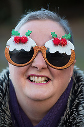 © Licensed to London News Pictures. 25/12/2016. Sutton Coldfield, West Midlands, UK. Due to the mild weather more swimmers than ever took part in the Sutton Coldfield Christmas morning swim. The morning plunge which takes place in Black Root pool has become an annual tradition. Pictured a supporter cheering on the swimmers. Photo credit: Dave Warren/LNP