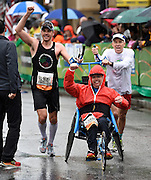Wheelchair Half Marathon racer Justin Knight, center, and his crew members John Rutledge, left and Paul Linck, clench their fists at the finish line to win their division Sunday, March 22, 2015, in Atlanta. David Tulis / AJC Special