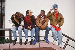 Multiracial group of teenagers sitting together on metal railings,