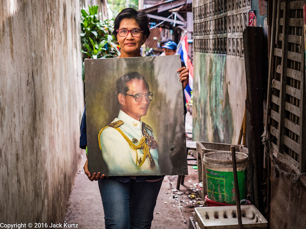 03 SEPTEMBER 2016 - BANGKOK, THAILAND:  A Pom Mahakan resident carries a portrait of Bhumibol Adulyadej, the King of Thailand, through the Pom Mahakan community. Hundreds of people from the Pom Mahakan community and other communities in Bangkok barricaded themselves in the Pom Mahakan Fort to prevent Bangkok officials from tearing down the homes in the community Saturday. The city had issued eviction notices and said they would reclaim the land in the historic fort from the community. People prevented the city workers from getting into the fort. After negotiations with community leaders, Bangkok officials were allowed to tear down 12 homes that had either been abandoned or whose owners had agreed to move. The remaining 44 families who live in the fort have vowed to stay.     PHOTO BY JACK KURTZ