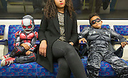 UNITED KINGDOM, London: 23 October 2015 Isley Greenland (Antman, left) and Tighe Greenland (Flacon, right) sit patiently on the underground as they make their way to the 2015 MCM London Comic Con which is being held at London's ExCel Arena. The event will be host to more than 110,000 comic con fans and cosplay enthusiasts over the weekend. Rick Findler / Story Picture Agency