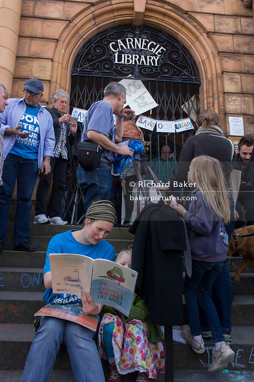 London, UK 2nd April: Artist Megan Roberts reads to a friend's daughter on the steps of the closed Carnegie Library, in Herne Hill, south London on 2nd April 2016. The angry local community in the south London borough have occupied their important resource for learning and social hub for the weekend. After a long campaign by locals, Lambeth have gone ahead and closed the library's doors for the last time because they say, cuts to their budget mean millions must be saved. A gym will replace the working library and while some of the 20,000 books on shelves will remain, no librarians will be present to administer it. London borough's budget cuts mean four of its 10 libraries will either close, move or be run by volunteers. ©Richard Baker / Alamy Live News.