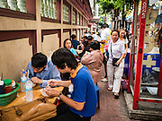 12 OCTOBER 2015 - BANGKOK, THAILAND:  People eat at tables set up on the sidewalk on the first day of the Vegetarian Festival in Bangkok's Chinatown. The Vegetarian Festival is celebrated throughout Thailand. It is the Thai version of the The Nine Emperor Gods Festival, a nine-day Taoist celebration beginning on the eve of 9th lunar month of the Chinese calendar. During a period of nine days, those who are participating in the festival dress all in white and abstain from eating meat, poultry, seafood, and dairy products. Vendors and proprietors of restaurants indicate that vegetarian food is for sale by putting a yellow flag out with Thai characters for meatless written on it in red.      PHOTO BY JACK KURTZ