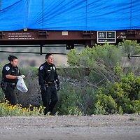 090314  Adron Gardner<br /> <br /> Gallup Police carry away objects from the scene of a train versus pedestrian accident near KFC east in Gallup Wednesday.
