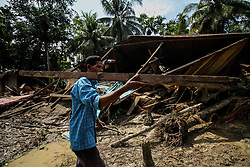 November 18, 2018 - Aceh, Aceh, Indonesia - A man collects debris from a house damaged after a flood caused by damage to a river embankment after heavy rains in North Aceh, on November 18, 2018, Aceh, Indonesia. (Credit Image: © Fachrul Reza/NurPhoto via ZUMA Press)